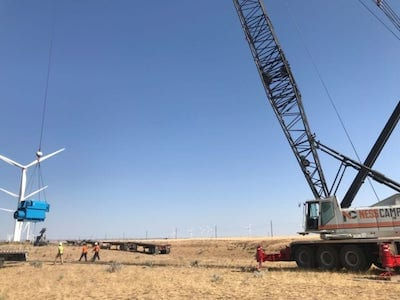 Crane lifting wind turbine blade on a wind farm