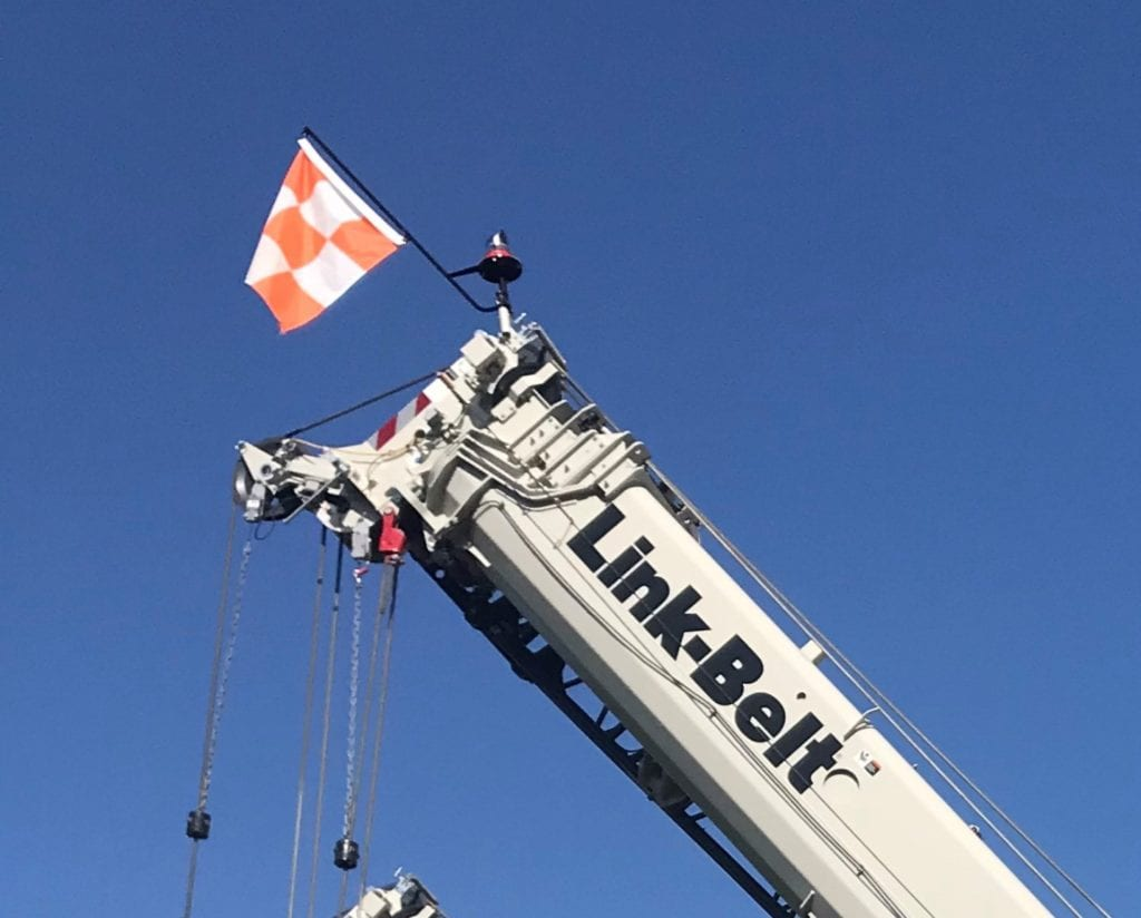 Orange and white checkered flag on a crane